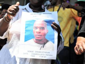 A mourner holds a poster of Mido Macia, who died after being dragged behind a police van. (Photo: Bongiwe Mchunu for he Star)