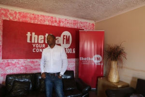 Programming Manager, Mochacho, stands proudly in front of Thetha FM's new logo