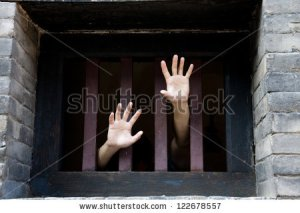 stock-photo-prisoner-hands-stretch-out-from-prison-bars-122678557