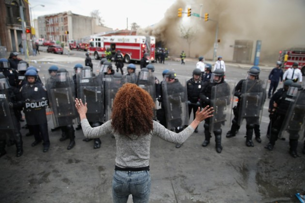 A woman faces down a line of Baltimore Police officers in riot gear during violent protests following the funeral of Freddie Gray April 27, 2015 in Baltimore, Maryland. (Photo by Chip Somodevilla/Getty Images) Accessed on http://www.pressroomvip.com/19-shocking-images-from-the-baltimore-riots/